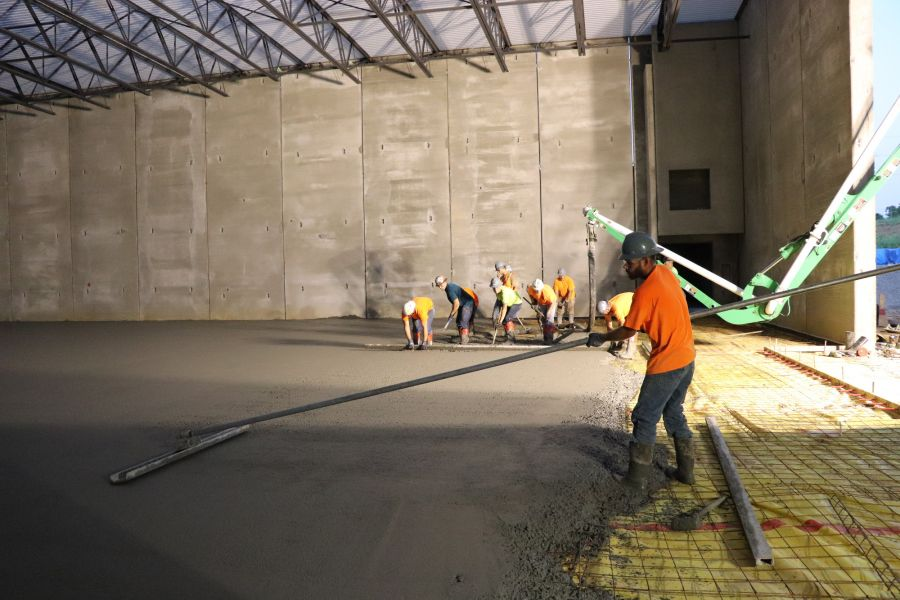 concrete contractors pouring structural concrete on wire mesh