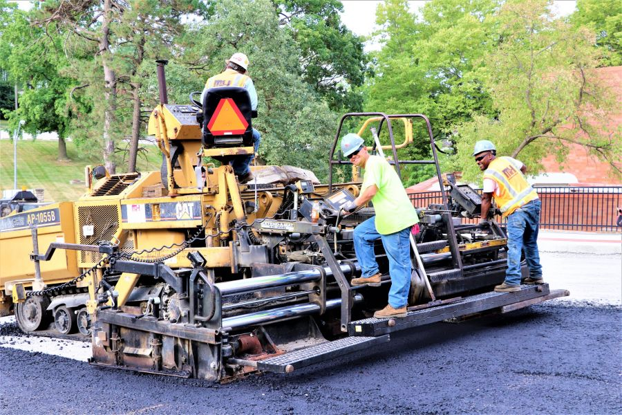 asphalt contractors smiling while laying asphalt paving