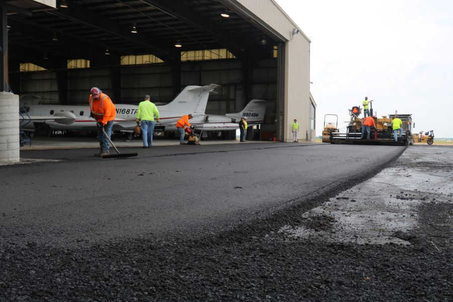 asphalt contractors with various tools to help smooth out the asphalts
