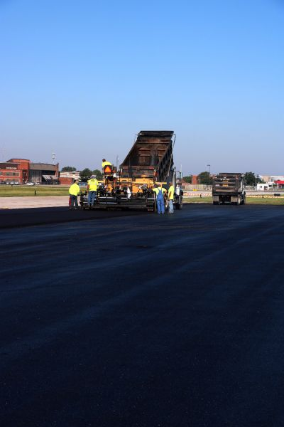 asphalt contractors pouring asphalt paving onto the New Century Airport Takeoff Area