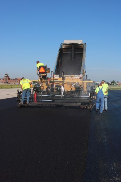 asphalt contractors laying asphalt paving using a asphalt paver
