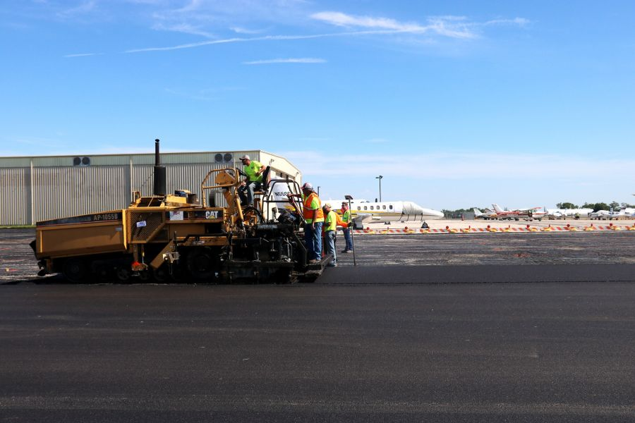 a asphalt paver and asphalt contractors laying asphalt at the New Century Airport