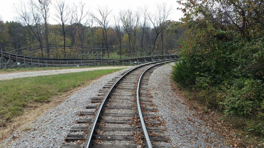 Railroad tracks on the ground near a roller coaster ride at World's of Fun