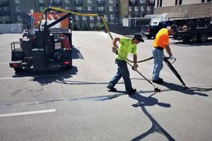 workers applying asphalt sealcoat